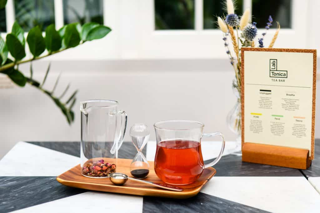 Cup of Lab Tonica herbal tea with a tea timer and tea menu
